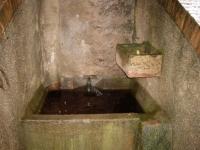 Imatge de la pica, el tub de ceràmica que sobeeixeix del dipòsit cisterna i el calaix per regar l'hort.